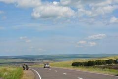 Motorrijderstoeristen op de weg in de steppen van Khakassia Stock Afbeeldingen