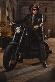 Motorrijderzitting op een koffie-raceauto motorfiets royalty-vrije stock fotografie