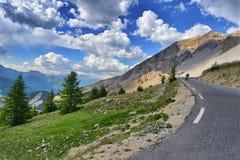 Motorruiter in de afstands achtermening over de rit in berglandschap onder bewolkte blauwe hemel Stock Foto's