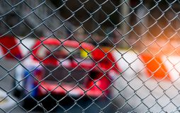 Motorsport car racing on asphalt road. View from the fence mesh netting on blurred car on racetrack background. Super racing car. On street circuit. Automotive royalty free stock photo