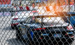 Motorsport car racing on asphalt road. View from the fence mesh netting on blurred car on racetrack background. Super racing car. On street circuit. Automotive royalty free stock photography