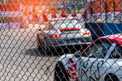 Motorsport car racing on asphalt road. View from the fence mesh netting on blurred car on racetrack background. Super racing car. On street circuit. Automotive stock image