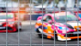 Motorsport car racing on asphalt road. View from the fence mesh netting on blurred car on racetrack background. Super racing car. On street circuit. Automotive royalty free stock image