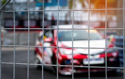 Motorsport car racing on asphalt road. View from the fence mesh netting on blurred car on racetrack background. Super racing car. On street circuit. Automotive stock images
