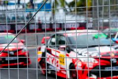 Motorsport car racing on asphalt road. View from the fence mesh netting on blurred car on racetrack background. Super racing car. On street circuit. Automotive royalty free stock photos