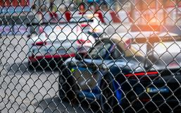 Motorsport car racing on asphalt road. View from the fence mesh netting on blurred car on racetrack background. Super racing car. On street circuit. Automotive stock photos