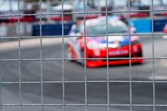 Motorsport car racing on asphalt road. View from the fence mesh netting on blurred car on racetrack background. Super racing car. On street circuit. Automotive royalty free stock images