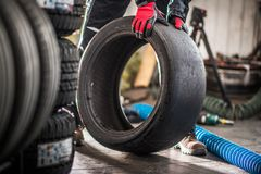 Motorsport Slick Tire. Caucasian Service Worker with Slick Racing Tire in Hands stock photos