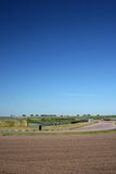 Motorsport Track. A motorsport track under a vivid blue (polarised) sky. The track comes in from the left towards the viewer with a corner marked by painted Stock Photos
