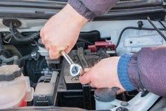 Motorteknikern byter ut bilbatteriet, d?rf?r att bilbatteriet t?mms ut begreppsbilunderh?ll fotografering för bildbyråer