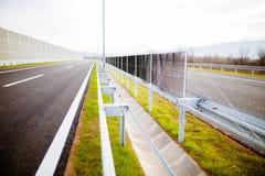 Motorväg på ängar för en ho för solig dag sceniska gröna Motorway som långdistans reser Asfalthuvudvägväg i lantligt platsbruksla arkivfoto