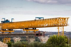 Motorway Bridge Construction. Motorway or autostrada bridge construction with large gantry crane lifting in road sections between pillars. Sicily, Italy stock images