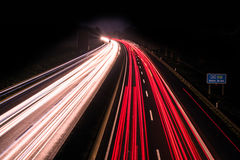Motorway at night with fast moving cars Royalty Free Stock Photography