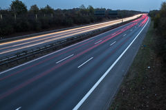 Motorway at night with fast moving cars Stock Image