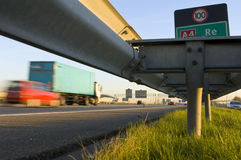 Motorway safety rail. A motorway safety rail with route information sign and motion blurred passing cars royalty free stock image