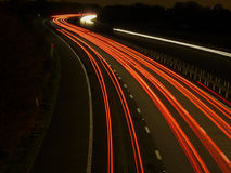 Motorway traffic rear light trails. Motorway traffic light trails receding into the distance Stock Photos