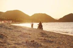 Motos d'équitation sur la plage au coucher du soleil Images stock