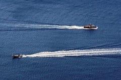 Motoscafi nella caldera che compone un paesaggio di OIA in Santorini fotografie stock