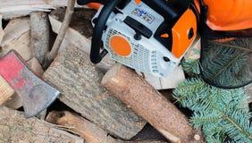 Motosega guidata benzina su una pila di legno immagine stock