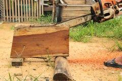 Motosierra de madera del sawing del hombre Imagenes de archivo