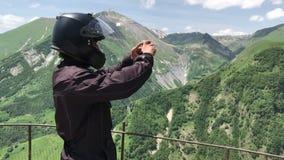 Mototurist do homem na posição do capacete da motocicleta na opinião do ponto no meio das montanhas do causacus e das imagens ver filme