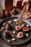 Motregenende honing op een plaat van fig. en amandelen stock afbeelding