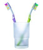 Motsättning: två färgrika tandborstar i exponeringsglas Arkivbilder