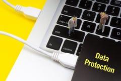 Mots écrits d'inscription de PROTECTION DES DONNÉES, ordinateur portable, unité de disque dur et miniature d'homme d'affaires photo libre de droits