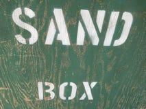 Mots écrits sur une boîte de sable Photographie stock libre de droits