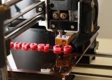 mots d'impression de l'imprimante 3D avec du plastique rouge Photos stock