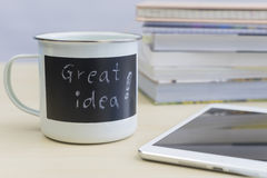 Mots de grande idée sur la tasse avec le comprimé et les livres Images stock