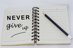 Mots de motivation JAMAIS GIVE UP écrit sur une page d'un carnet ouvert avec le crayon près de lui Photographie stock