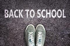 Mots de nouveau à l'école écrite sur la route goudronnée avec des chaussures d'espadrilles, au lycée et au concept d'université Photos stock