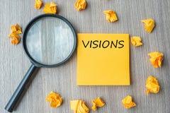 Mots de vision sur la note jaune avec le papier et la loupe emiettés sur le fond en bois de table SEO, idée, but, stratégie, images libres de droits
