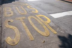 Mots jaunes d'arrêt d'autobus écrits sur la rue à Macao Images libres de droits