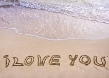 Mots JE T'AIME écrits sur le sable, avec des vagues à l'arrière-plan Photo libre de droits