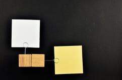 Motsatt åsikt, två pappers- anmärkningar på svart för presentation Arkivbild