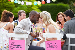 Mottagande för brud- och brudgumEnjoying Meal At bröllop Arkivfoto