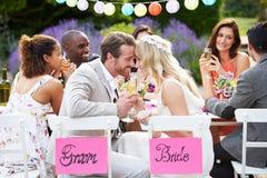 Mottagande för brud- och brudgumEnjoying Meal At bröllop Royaltyfria Bilder