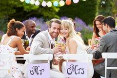 Mottagande för brud- och brudgumEnjoying Meal At bröllop arkivfoton