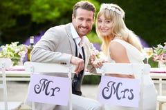 Mottagande för brud- och brudgumEnjoying Meal At bröllop Royaltyfri Fotografi