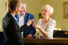 Mottagande - gäster kontrollerar in ett hotell Royaltyfri Foto