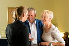 Mottagande - gäster kontrollerar in ett hotell Royaltyfri Fotografi
