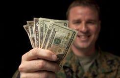 mottar militära pengar för den lyckliga mannen royaltyfri bild
