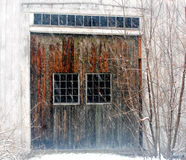 Mottled Barn door in a snow storm in December on a dirty white New England barn. Snowing 2 4x4 window paned barn doors small windows over door stock images