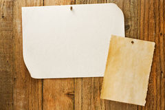 Mottled beige paper naled to distressed wooden wall. Mottled beige parchment paper posters similar to the grungy cowboy wanted notices nailed to vintage wooden Stock Photo