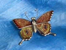 Motylie błyskotki ob błękita tkaniny Zdjęcia Stock