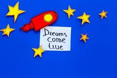 Motywacyjny plakat Sen przychodzą prawdziwego ręki literowanie przy błękitnym kosmosu tłem z rakiety i gwiazd odgórnego widoku ko zdjęcia royalty free
