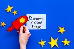 Motywacyjny plakat Sen przychodzą prawdziwego ręki literowanie przy błękitnym kosmosu tłem z rakiety i gwiazd odgórnego widoku ko obraz royalty free