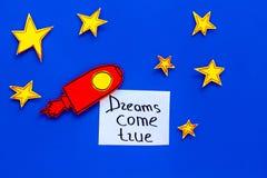 Motywacyjny plakat Sen przychodzą prawdziwego ręki literowanie przy błękitnym kosmosu tłem z rakiety i gwiazd odgórnego widoku ko zdjęcia stock